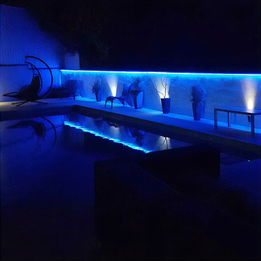 Moody blue lighting effect in a dark indoor pool room using Eleni Lighting EL501 linear profile cornices