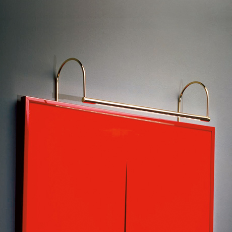 Sleek contemporary designer LED picture light in brass, illuminating a piece of red modern art
