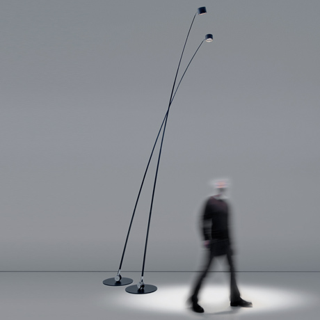 Pair of extra tall minimal and contemporary Davide Groppi Sampei LED Floor Lamp, illuminating a blurred person below