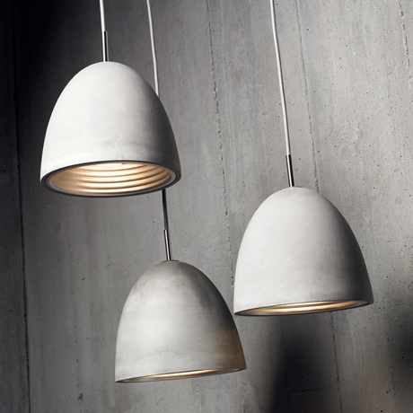 Three modern Seed Design Castle Concrete Dome pendants, hung against an industrial concrete wall