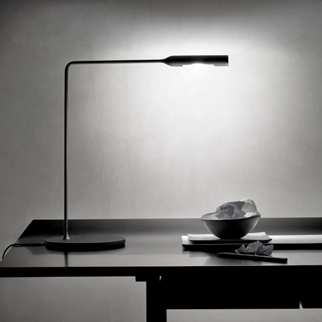Modern minimal black LED desk lamp lighting a contemporary desk
