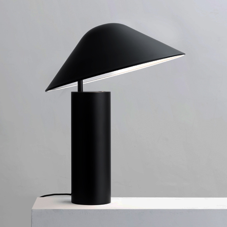 Modern and minimal, the Damo table lamp in black by Seed Design lighting a shelf