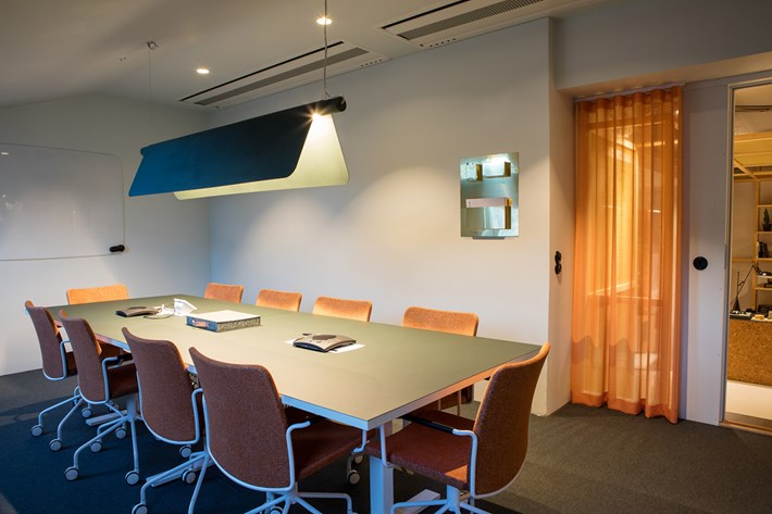 Blond Belysning Bend pendant in blue, set over a large meeting table in Morris Law offices in Sweden