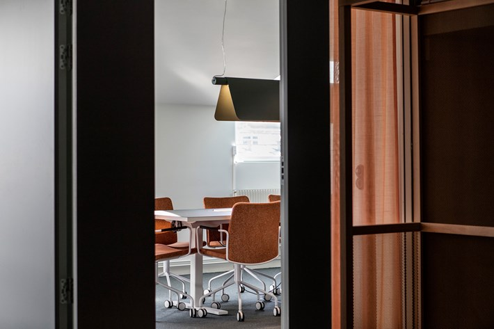 Blond Belysning Bend pendant in blue, viewed from the hallway over a meeting table in Morris Law offices in Sweden