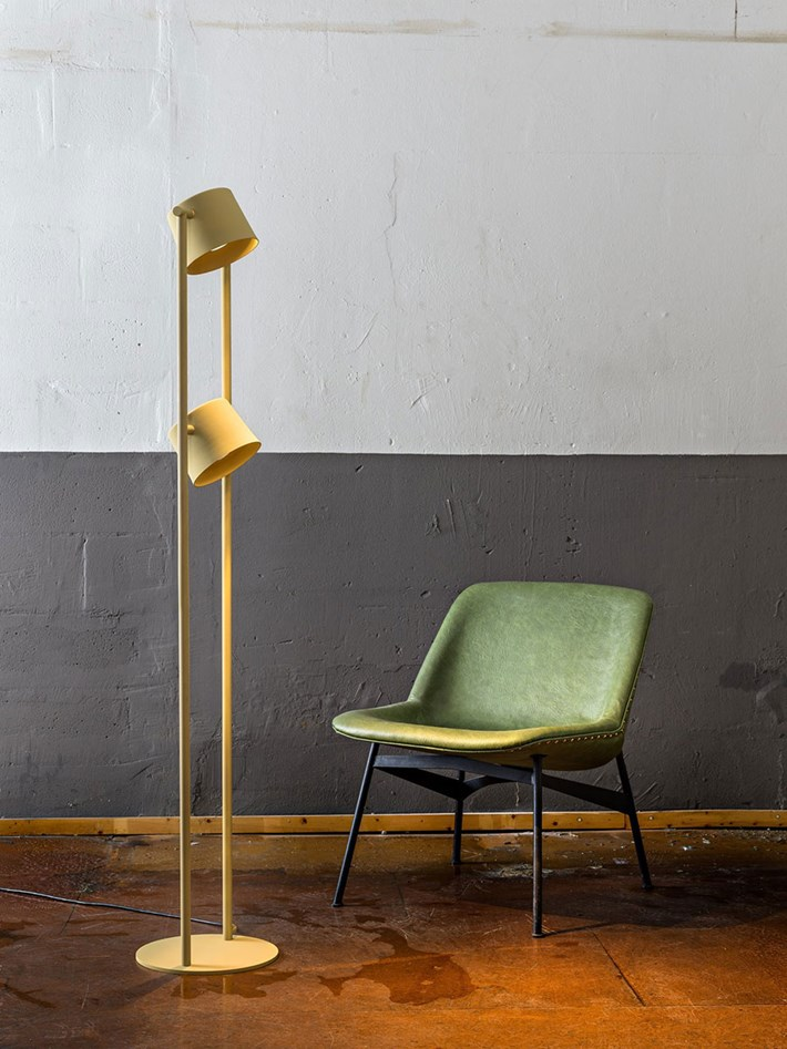 Blond Belysning Chorus Floor Lamp with twin shades in yellow in an industrial room with a green mid century chair