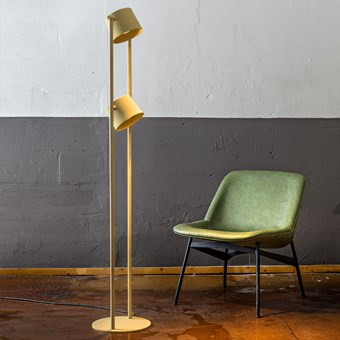 Blond Belysning Chorus Floor Lamp in yellow in an industrial room with a green mid century chair