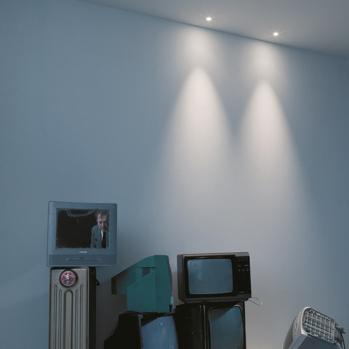 The Baba Evo R6 Recessed Downlight by Flexalighting, illuminating tv's in a blue/grey room.