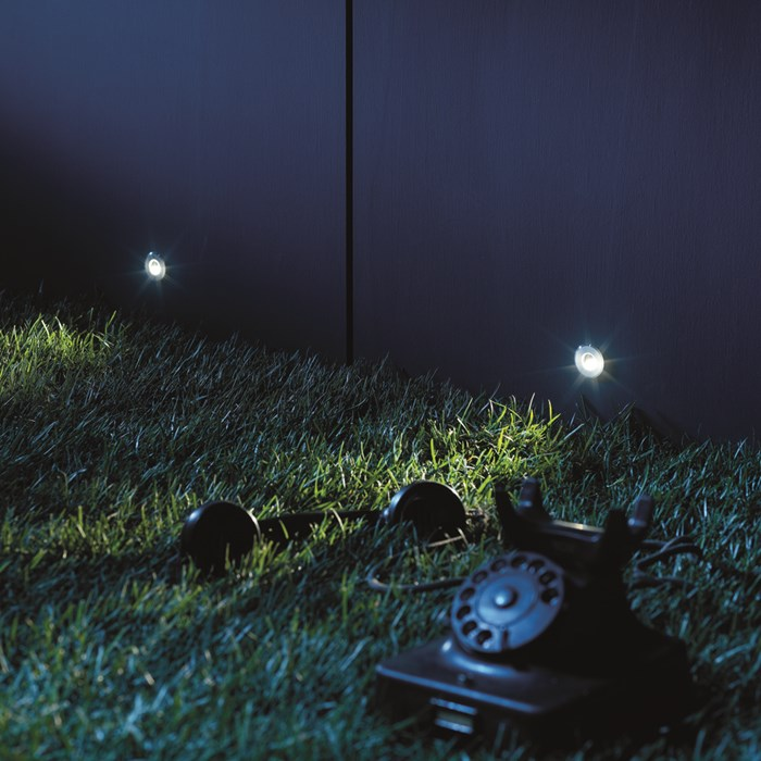 Mood shot image of two Flexalighting Bean LED Recessed Step Lights, illuminating a garden.