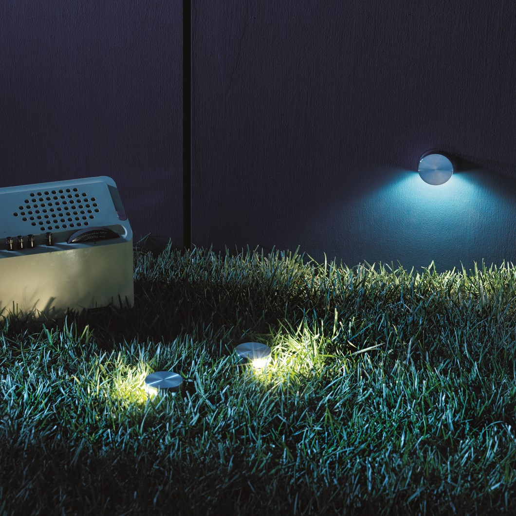 3 Flexalighting Bunga Path Lights shown installed in the ground and wall, lighting a garden area.