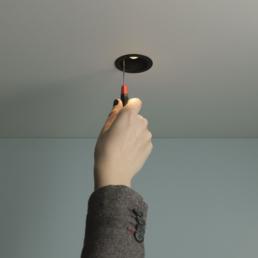 The Flexalighting Jimbo 2 LED Downlight lifestyle image in black with a woman adjusting the optic.
