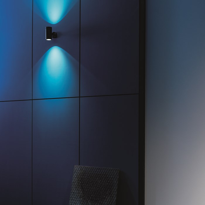 Lifestyle image of the Flexalighting Keller Double Emission wall light illuminating a blue wall outside.