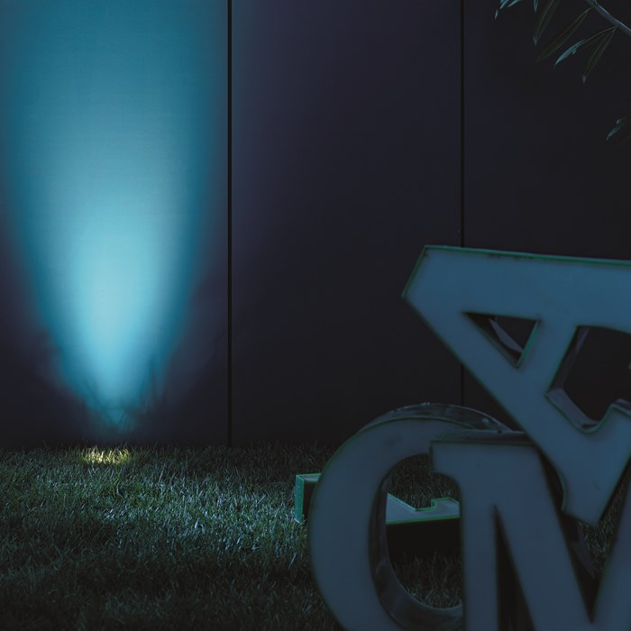 Landa Uplights by Flexalighting in a lifestyle image, highlighting a blue outdoor wall.