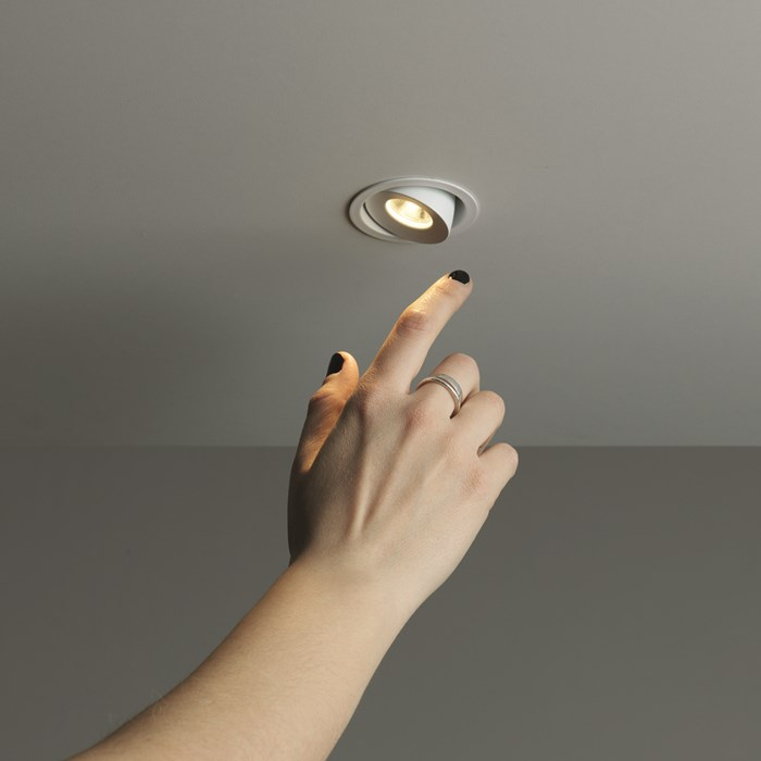 Lifestyle image of the Mine 6 LED downlight, adjusted at an angle and shown in proportion to a human hand.