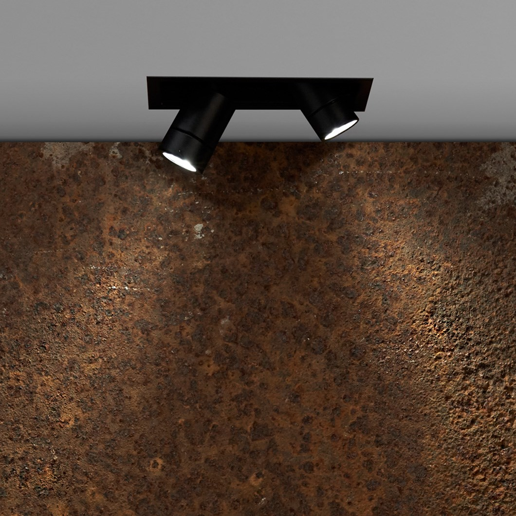 Flexalighting's Minileda QX120 in a lifestyle image, shining a rusty concrete wall.