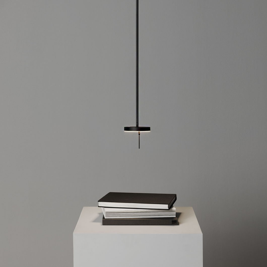 Lifestyle image of the Grok Invisible Pendant in black, hanging over a table and lighting 3 work books.