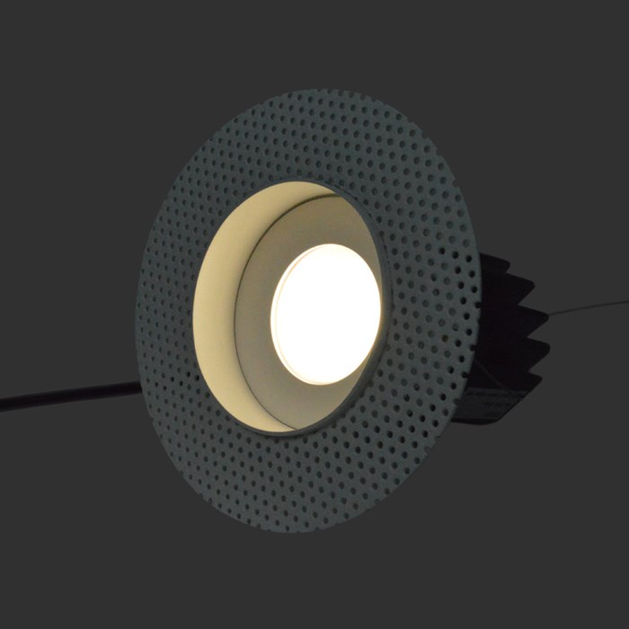 Three quarter view of DLD Eiger Mini True Colour CRI98 LED downlight with plaster-in frame switched on against a dark background