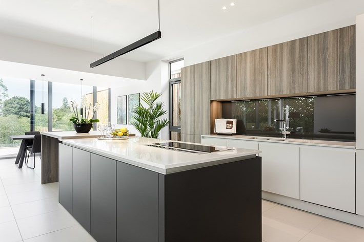 Wide shot of DLD Shadowline LED track suspended over the kitchen island in a contemporary modern interior open plan living and kitchen space