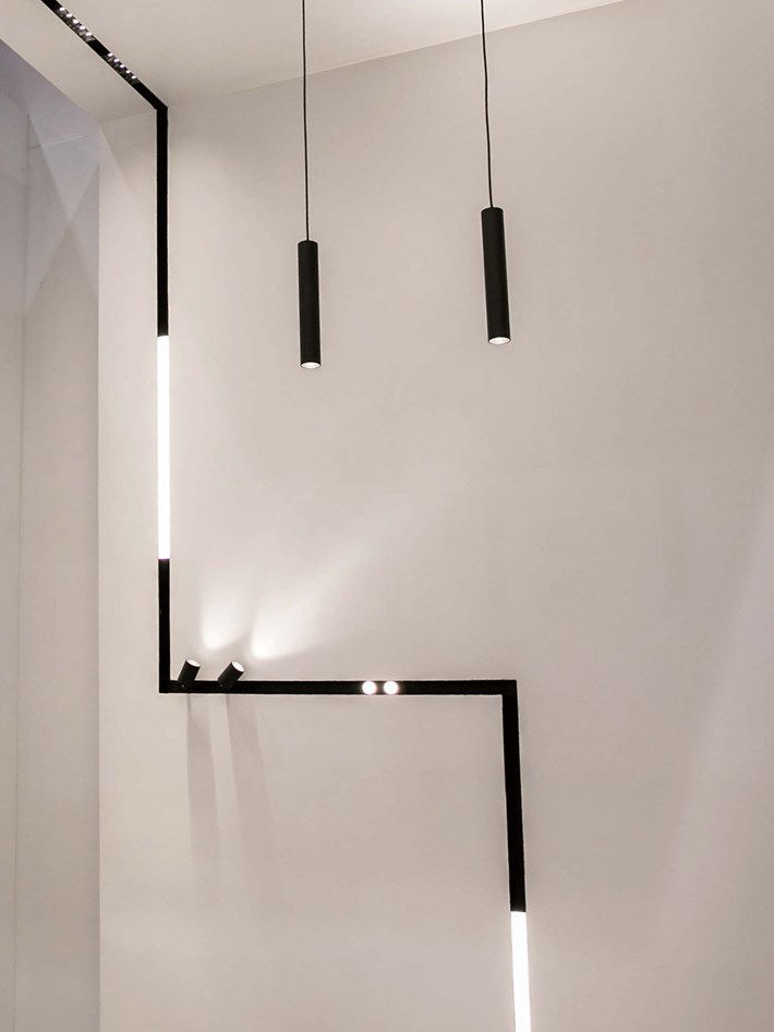 DLD Shadowline recessed track with right angle joints linking from the ceiling to the wall, using linear LED modules, spot lights, pendants and downlights