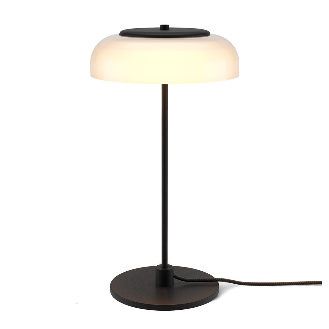The Nuura Blossi Table Lamp in black, turned on.