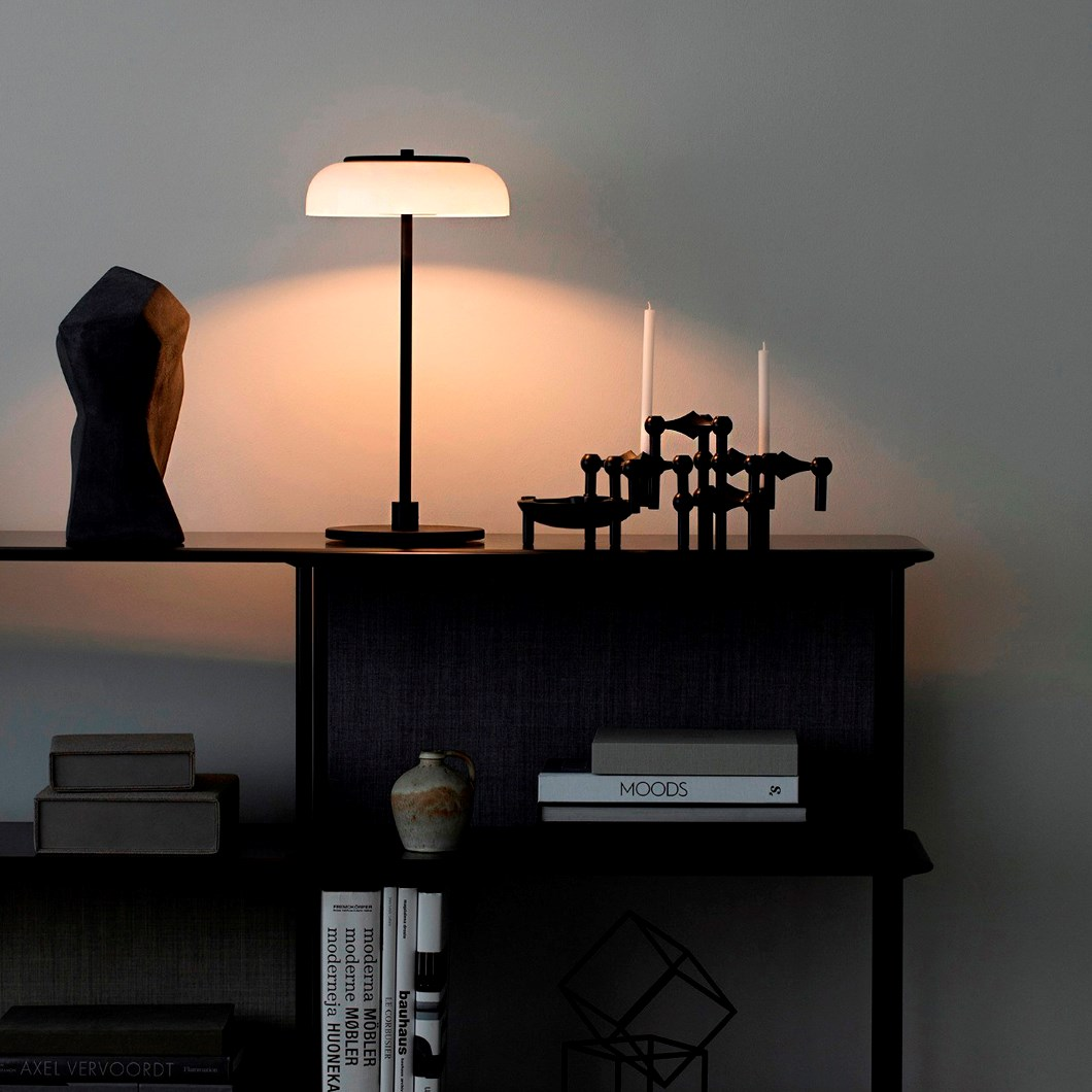 The Nuura Blossi Table Lamp in black, in a roomshot on top of a dark cabinet.