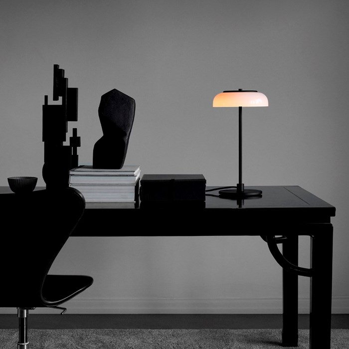 The Nuura Blossi Table Lamp in black, on a dark table in a home study area.