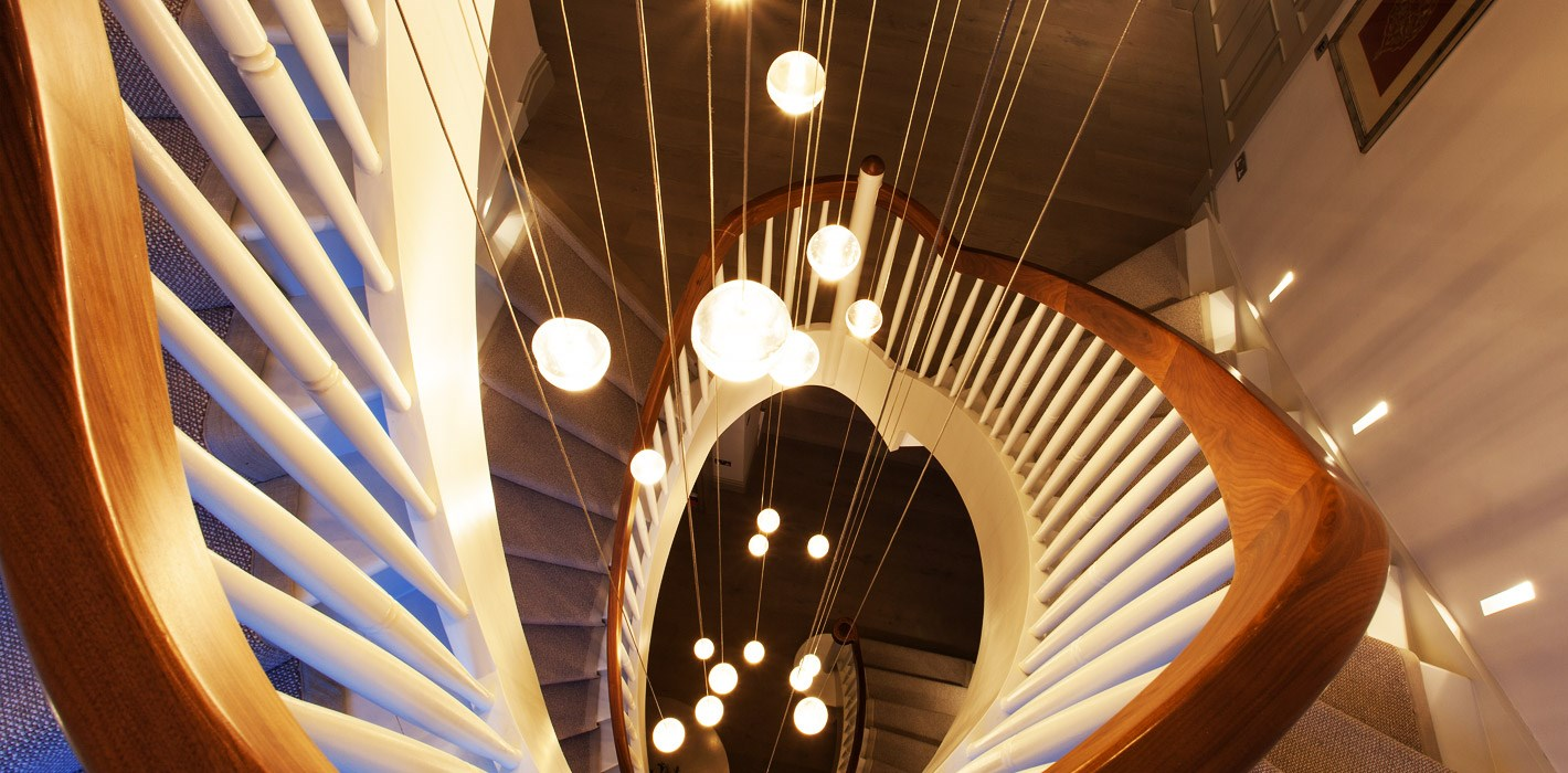 Lighting Design - cluster of Bocci pendants suspended at multiple levels down a 3 storey spiral staircase