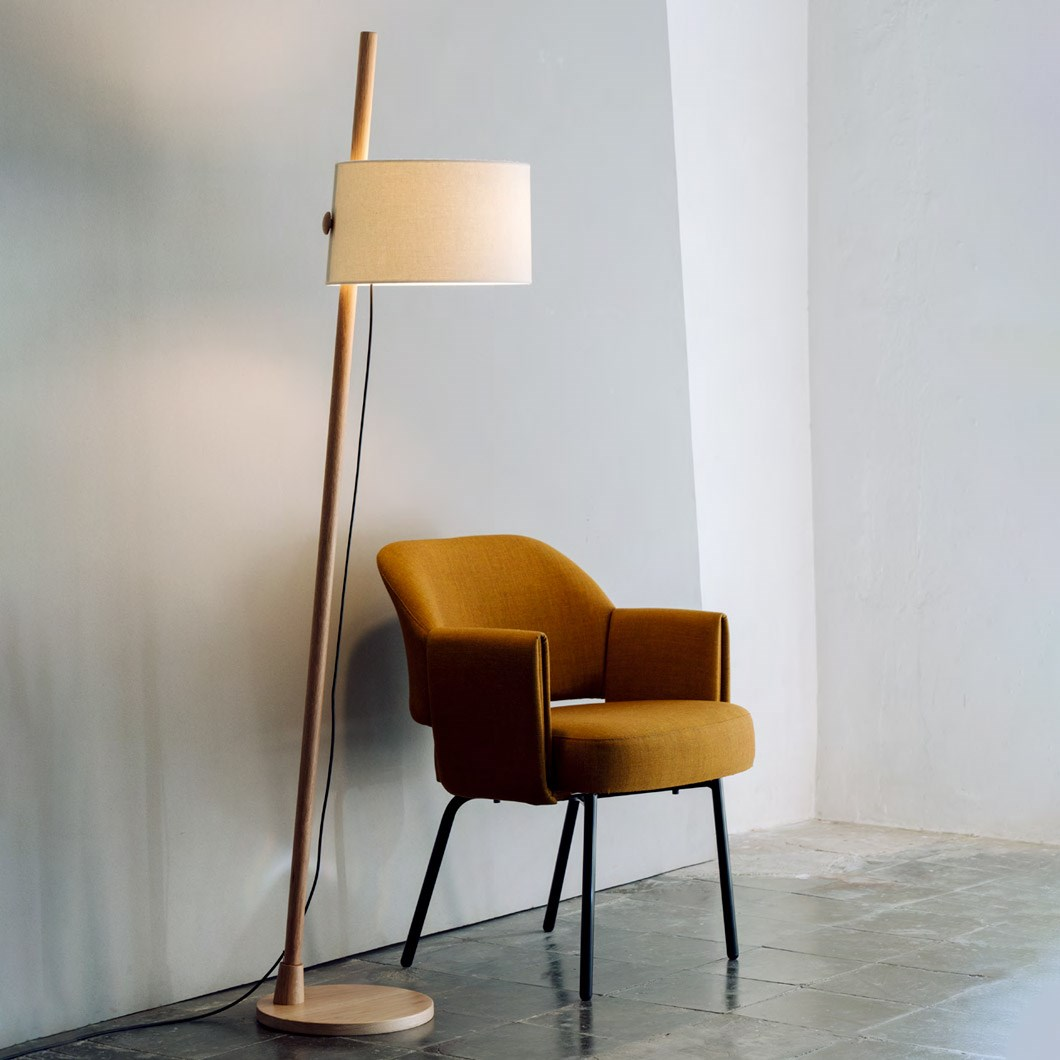 Milan Iluminacion Linood Floor Lamp with slanted base in oak in a contemporary space next to a mid century mustard fabric armchair