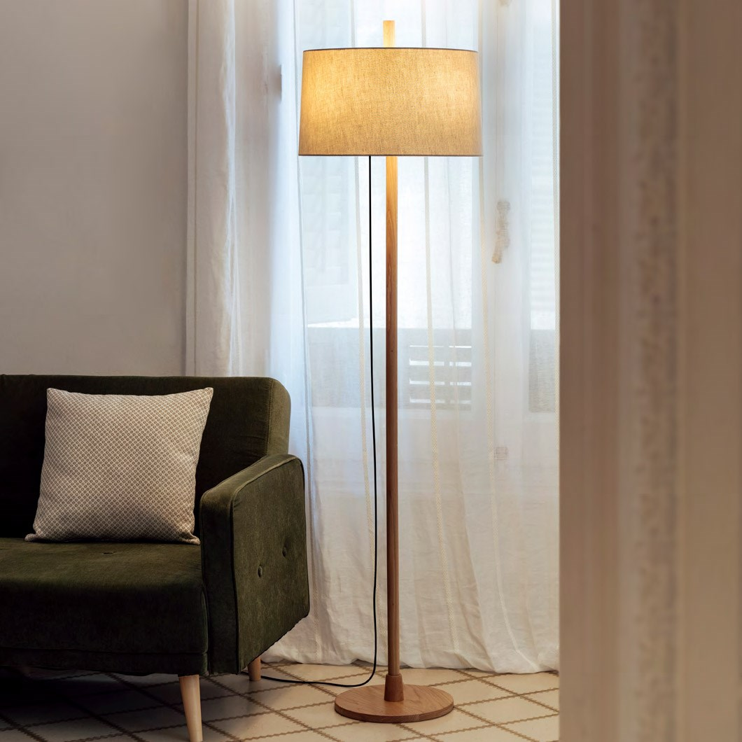 Milan Iluminacion Linood Straight Floor Lamp in oak in a modern living room next to a mid century green fabric sofa